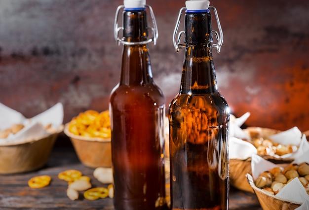 Zwei bierflaschen, teller mit pistazien, kleine brezeln und erdnüsse. lebensmittel- und getränkekonzept
