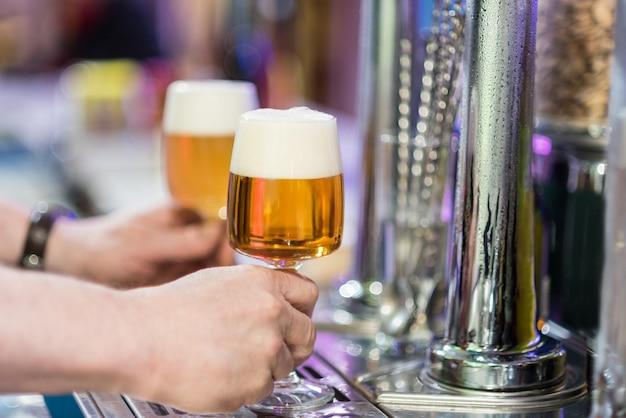 Zwei biergläser im hahn einer kneipe
