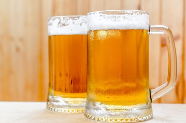 Zwei bierkrüge auf holz