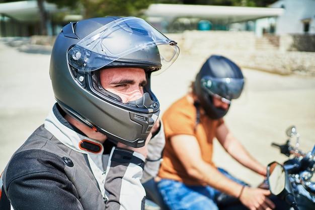 Zwei biker setzen auf den motorrädern helm auf