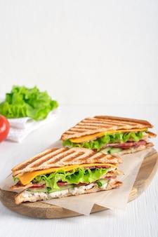 Zwei bio-sandwiches mit schinken-käse-salat und geröstetem brot, serviert auf schneidebrett in der küche
