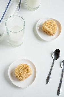 Zwei biskuitkuchen mit sahne auf weißen tellern mit gläsern milch, löffeln und einer serviette mit blauen streifen auf weißem hintergrund.