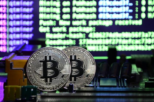 Zwei bitcoins liegen auf einer videokartenoberfläche mit hintergrund der bildschirmanzeige