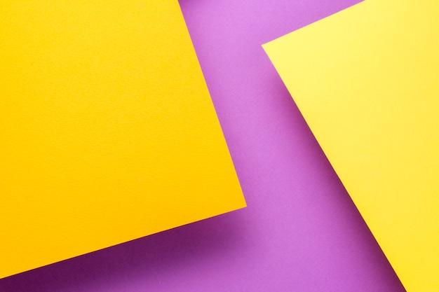 Zwei blätter gelbes und orangefarbenes papier steigen über dem purpurroten hintergrund an. die blätter werfen einen schatten.