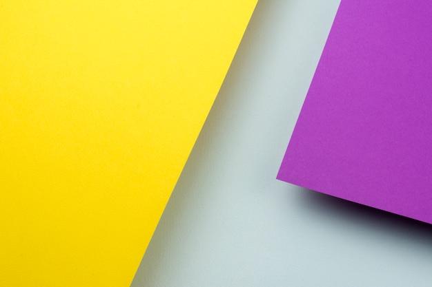 Zwei blätter gelbes und purpurrotes papier steigen über dem blauen hintergrund an.