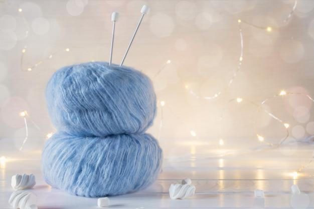 Zwei blaue, flauschige ballgarne und stricknadeln.