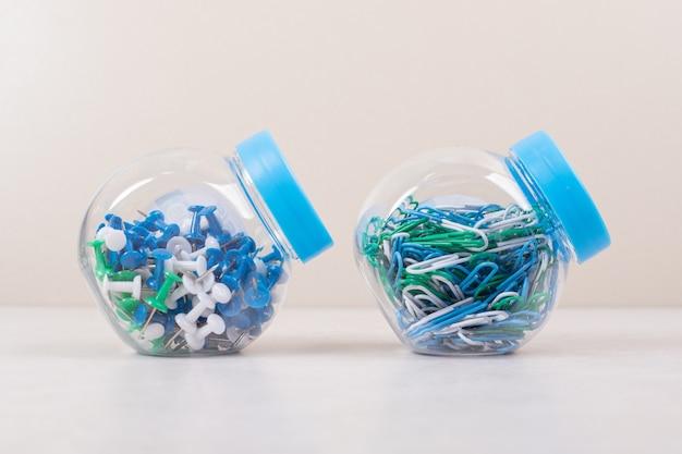 Zwei blaue gläser voller bunter stifte und büroklammern auf beigem hintergrund. hochwertiges foto