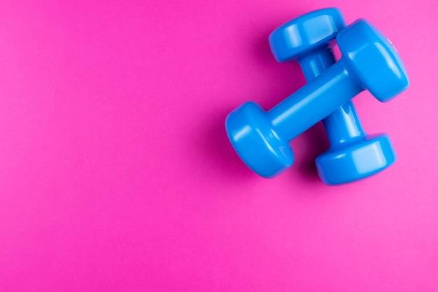 Zwei blaue hanteln auf einem rosa hintergrund, fotobanner, draufsicht, raum für text.