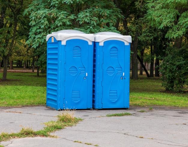 Zwei blaue kabinen der bio-toilette