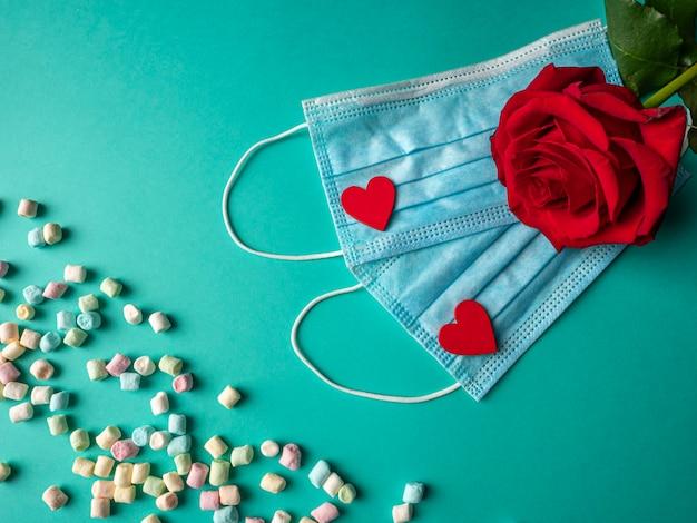 Zwei blaue masken mit zwei roten herzen und einer roten rose auf masken und bunten bonbons auf grün