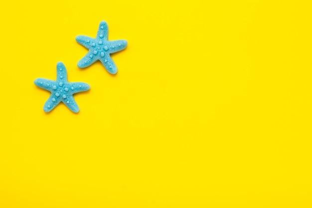 Zwei blaue plastikstarfishes auf einem gelben hintergrund. ansicht von oben. platz für text