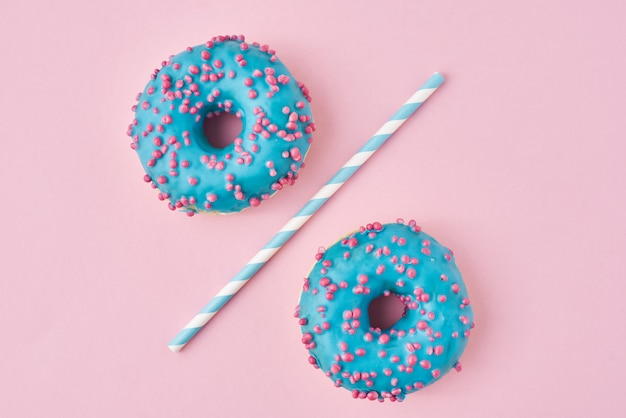 Zwei blaue schaumgummiringe trennten sich mit trinkhalm auf rosa hintergrund. kreatives lebensmittelkonzept