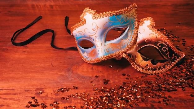 Zwei blaue und goldene karnevalsmaske mit funkelnden pailletten auf hölzernem schreibtisch