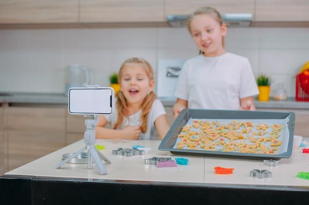 Zwei bloggerinnen machen cookies und filmen trainingsvideos auf einem smartphone.