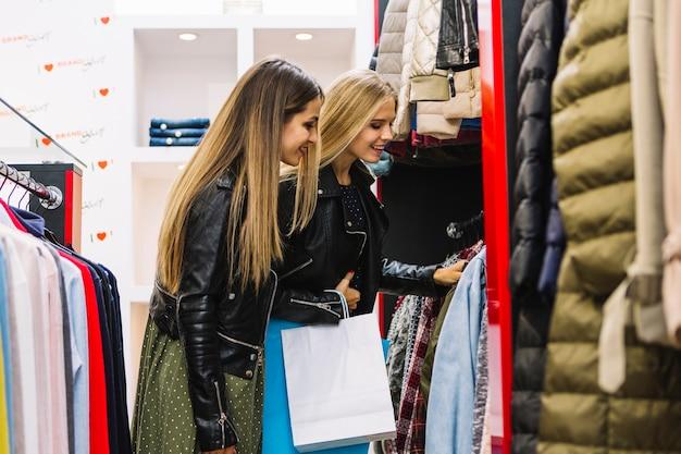 Zwei blonde junge frauen, die kleidung im einkaufsspeicher betrachten