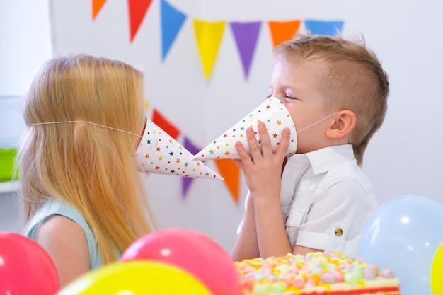 Zwei blonde kaukasische kinder junge und mädchen, die den spaß spielt mit hüten an der geburtstagsfeier haben. bunter hintergrund mit ballonen