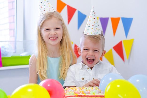 Zwei blonde kaukasische kinder junge und mädchen, die spaß haben und an der geburtstagsfeier lachen. bunter hintergrund mit ballonen und geburtstagsregenbogenkuchen.
