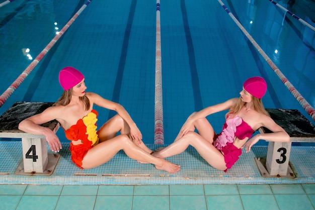 Zwei blonde schlanke junge stylische frauen in bunten badeanzügen und rosa schwimmmützen am pool