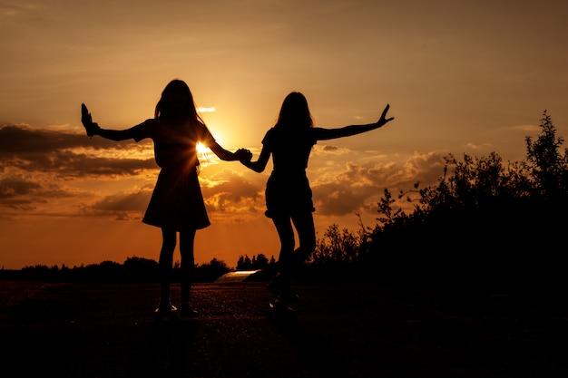 Zwei blonde teenager fahren skateboards bei schönem sonnenuntergang