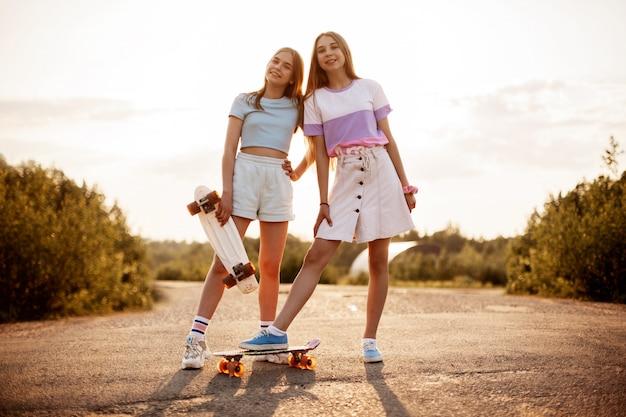 Zwei blonde teenager-mädchen in hipster-kleidung mit einem skateboard in einem sommerpark an der frischen luft