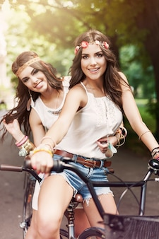 Zwei boho-mädchen, die fahrrad fahren