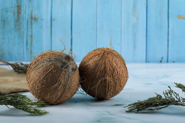 Zwei braune kokosnussfrüchte auf marmoroberfläche