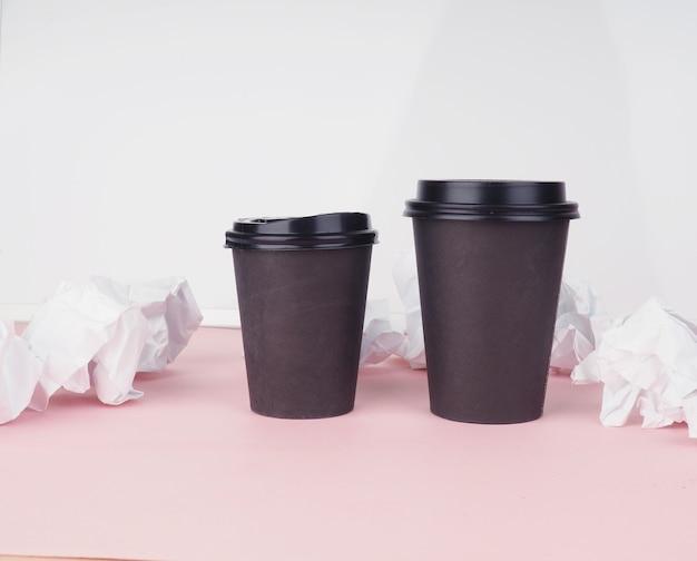 Zwei braune pappkaffeetassen auf einem rosa tisch, zerknittertes papier daneben.
