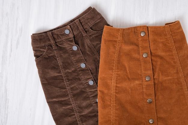Zwei braune röcke auf einem holztisch. modekonzept