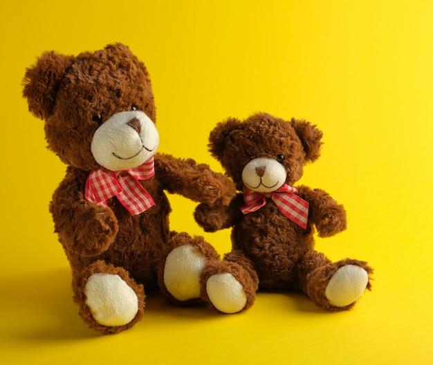 Zwei braune teddybären auf gelb