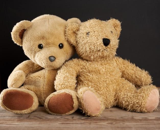 Zwei braune teddybären sitzen auf einem braunen holztisch