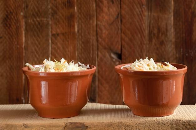 Zwei braune tontöpfe mit fermentiertem kohl