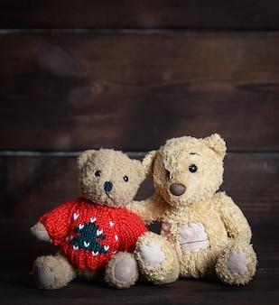 Zwei braune weiche teddybären sitzen auf holzoberfläche