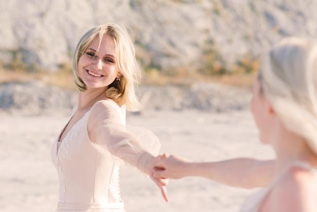 Zwei brautfrauen im weißen kleid mit blonden haaren umarmen sich, lesbische hochzeit