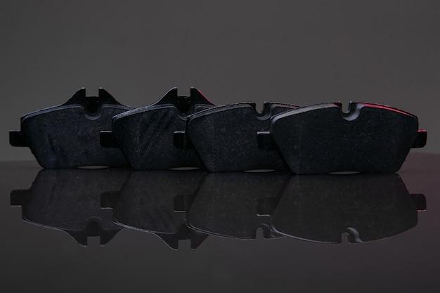 Zwei bremsbeläge für einen supersportwagen auf dunklem hintergrund mit roter beleuchtung