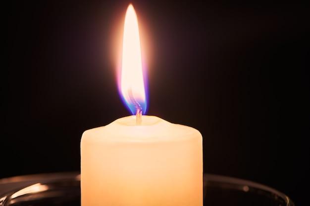 Zwei brennende kerzen auf dem tisch in der nachtdunkelheit. flamme der hoffnung und erinnerung. nahaufnahme mit kopienraum.