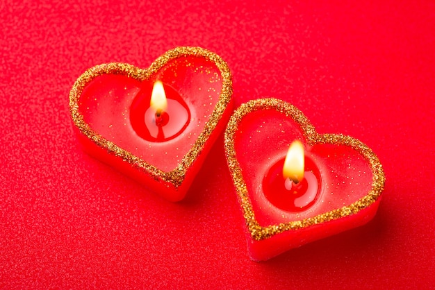 Zwei brennende rote herzkerzen auf rotem hintergrund