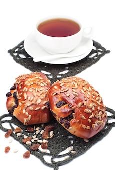 Zwei brötchen mit rosinen und sonnenblumenkernen und eine tasse tee auf weißem hintergrund