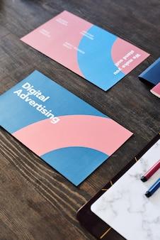 Zwei broschüren mit digitalem werbekurzkurs umgeben von textmarkern auf leerem papier in der zwischenablage und blauem ordner auf dem tisch