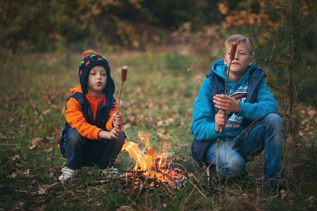 Zwei brüder braten hotdogs auf stöcken über flammen in einem lagerfeuer. familienurlaub in der natur.
