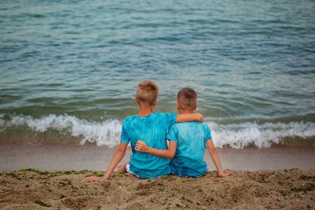 Zwei brüder, die auf seestrand am sommertag sitzen.