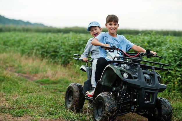 Zwei brüder, die ein vierrädriges atv-quad-bike fahren. glückliche kindermomente.