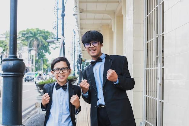 Zwei brüder, die vintage schwarzen anzug tragen posieren und lächeln, während sie erfolg oder ja-geste zeigen