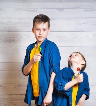 Zwei brüder in gelben t-shirts und blauen hemden mit bunten lutschern. entzückende jungs haben viel spaß beim lutscher lecken