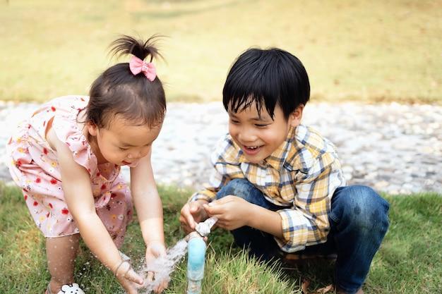 Zwei brüder und schwestern spielen wasser aus dem wasserhahn