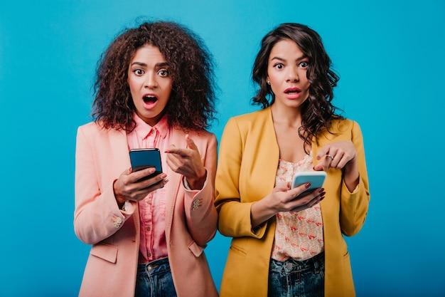 Zwei brünette frauen, die smartphones halten