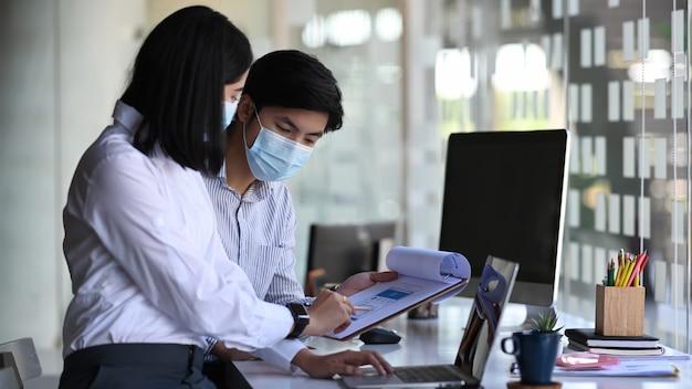 Zwei büroangestellte, die eine medizinische maske tragen und die idee des projekts in einem modernen büro diskutieren.