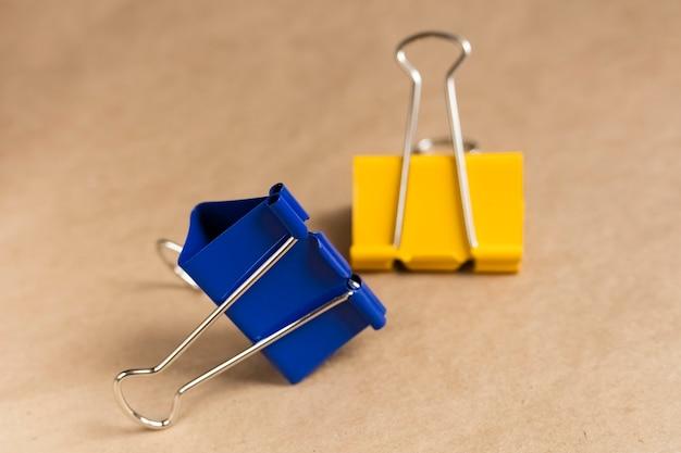 Zwei büroklammern blau und gelb auf braunem hintergrund. nahaufnahme. hintergrund, bastelpapier