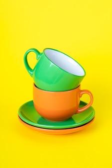 Zwei bunte leere teetassen und untertassen. satzgeschirr, eine sammlung von kaffeetassen, eine reihe von bechern.
