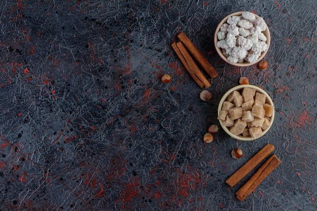 Zwei bunte schalen voller süßer weißer und brauner bonbons mit gesunden nüssen und zimtstangen.