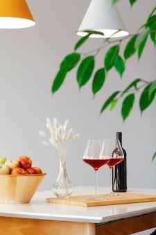 Zwei burgunderfarbene gläser rotwein, holzschale mit grünen und roten äpfeln, dekorvase auf tisch in der küche